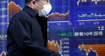 Hombre en frente de una pizarra que muestra la caída de las acciones en Bolsa asiática