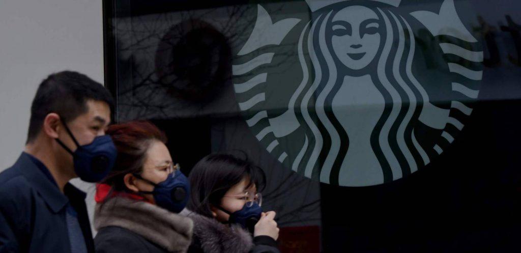 Ciudadanos chinos con tapabocas en frente de un Starbucks